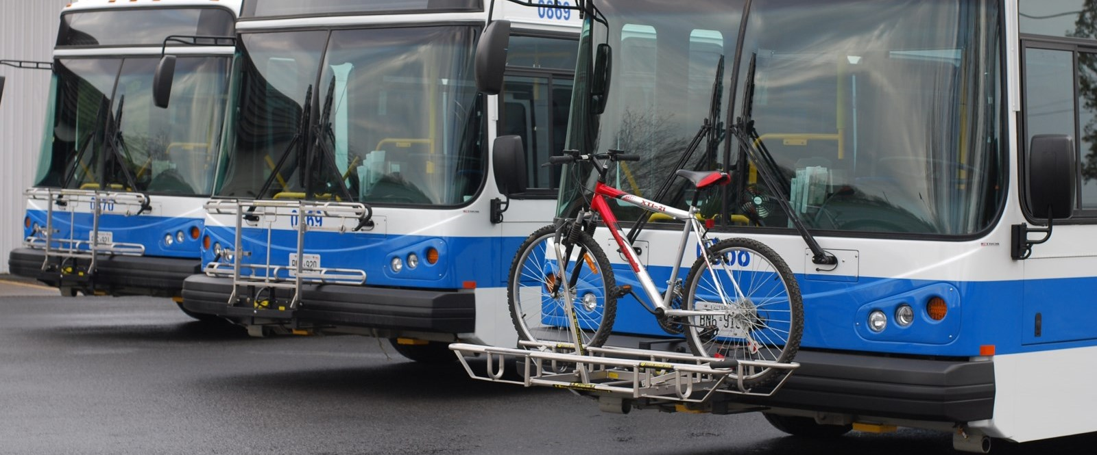 Cornwall Three buses lined up with bike racks