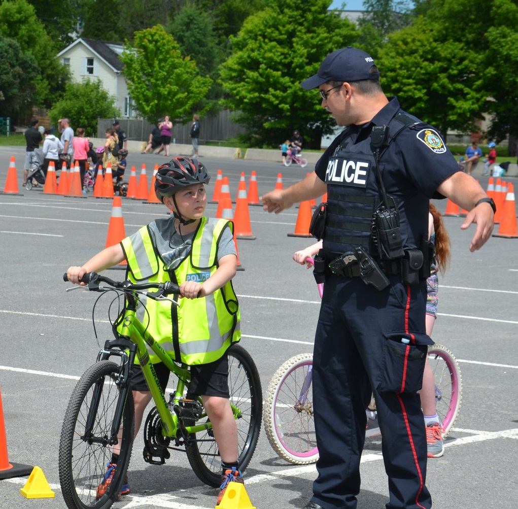 Cornwall Community Police officer gestures while instructing a young bike rider