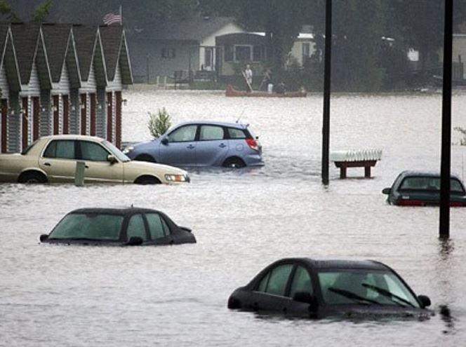 Cars and buildings flooded during heavy rain storm.
