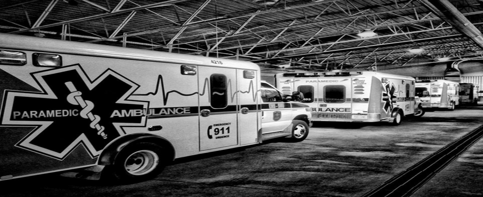 Black and white photo of ambulances in garage