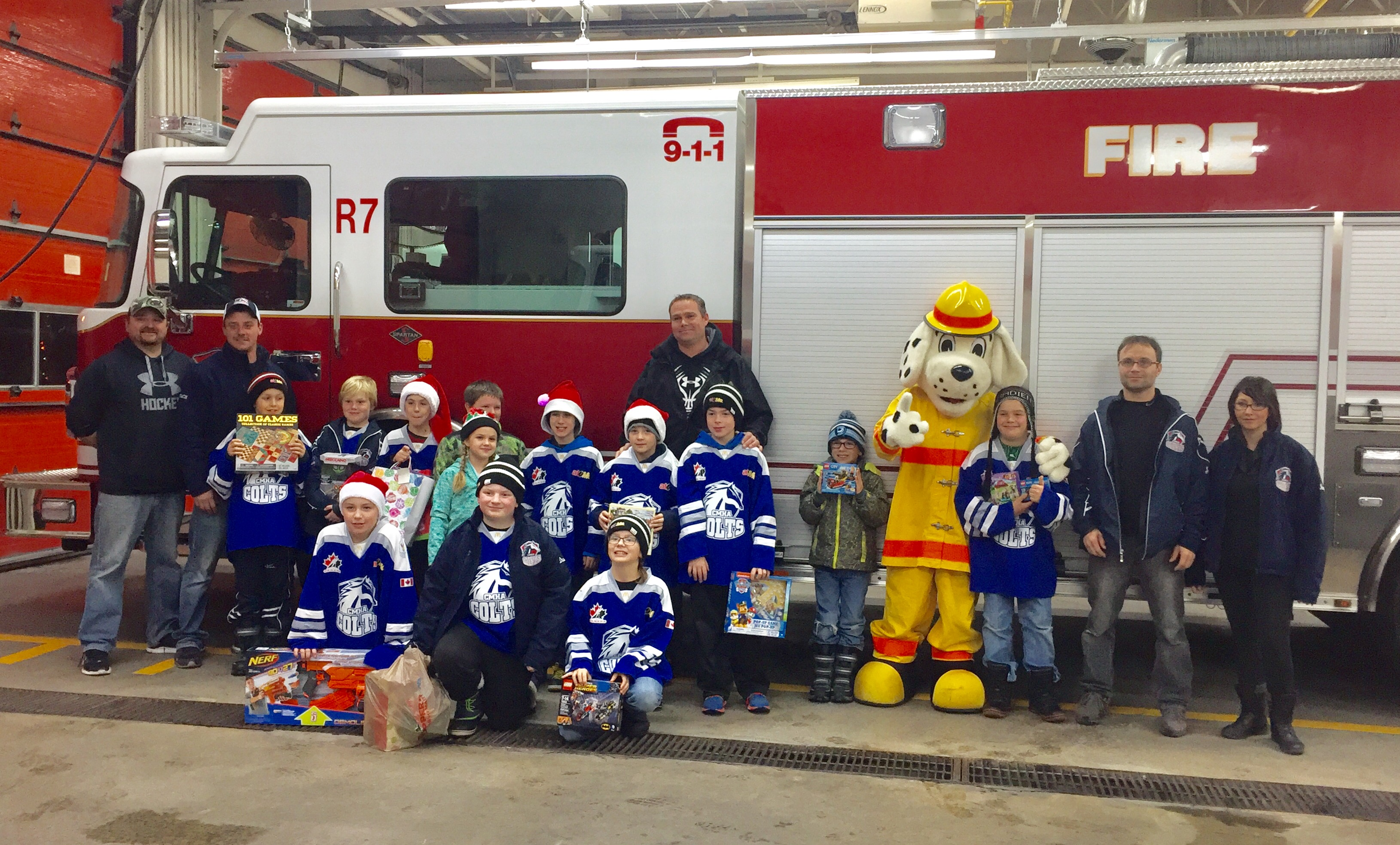Children stand in front of fire truck with blue jerseys on