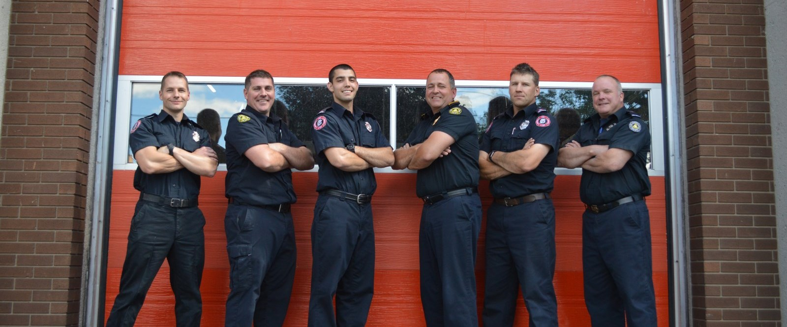 Firefighters stand with arms crossed in front of HQ