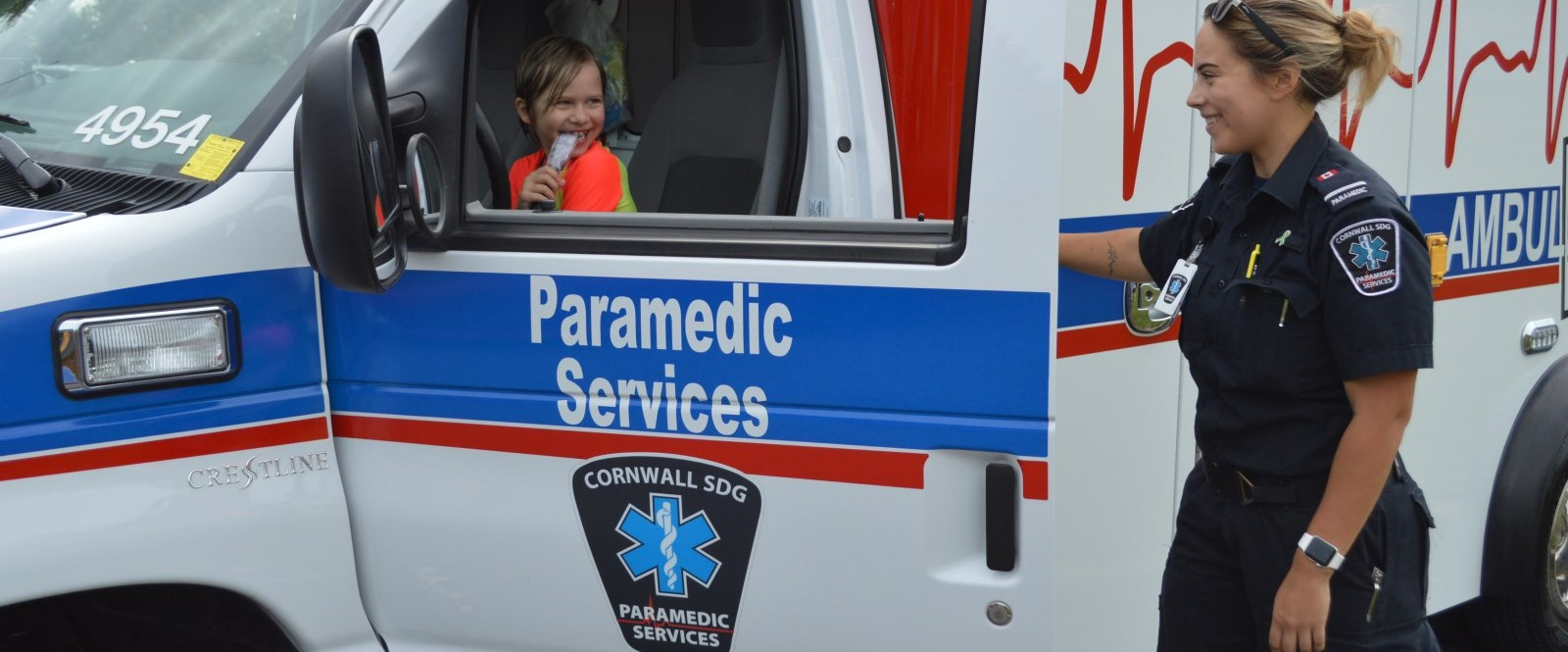 Paramedic smiling at child behind wheel of ambulance