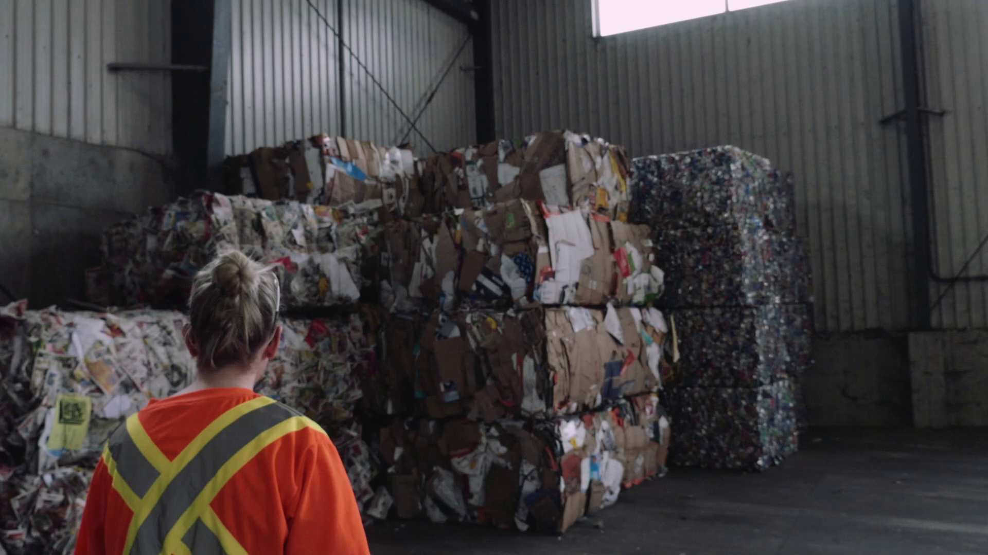A person giving a tour of the recycling facility