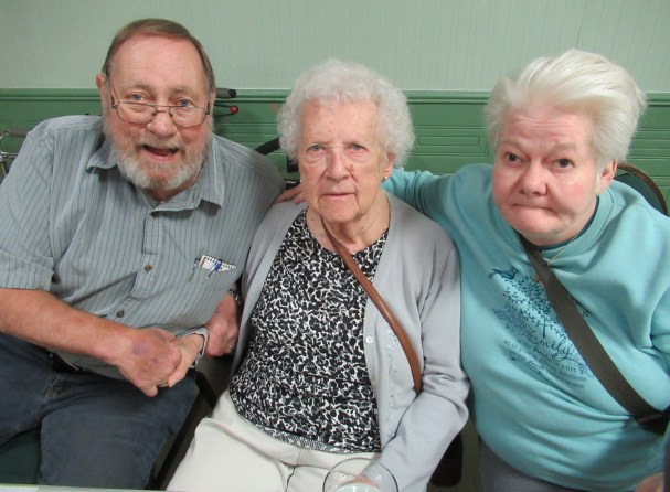 Three seniors sit together to pose for photo