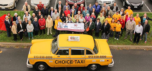 Volunteers stand with Choice Taxi after donation