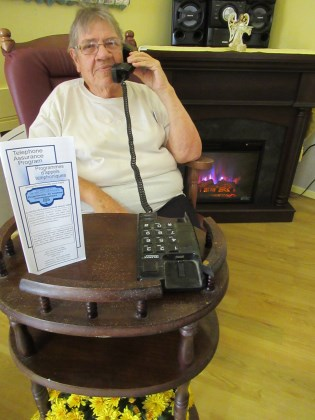 Senior on phone in chair by fireplace