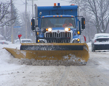 Blue plow clears snow from City of Cornwall street