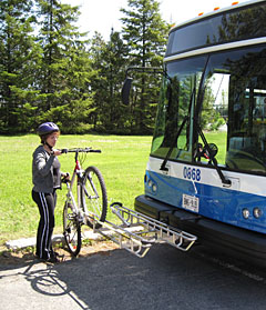 Passenger loads bicycle onto bus' front rack