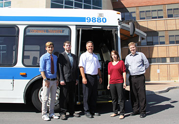 College students stand outside a Cornwall Transit bus