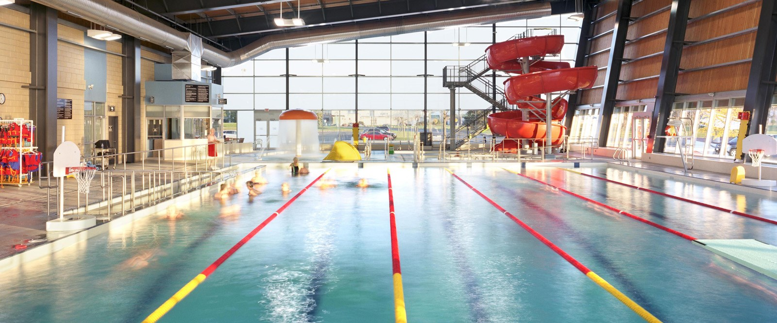 View of inside of Cornwall Aquatic Centre with children swimming on left edge of main pool
