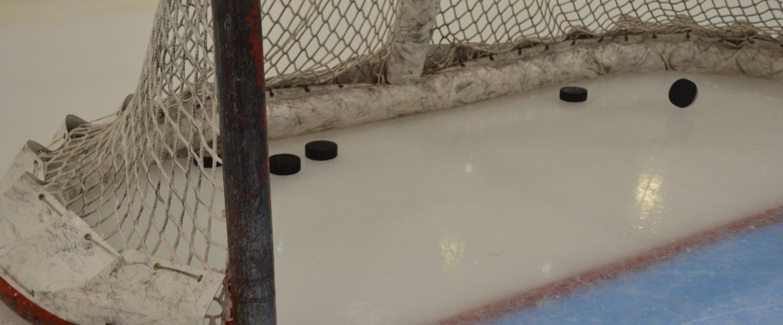 Several pucks sit inside hockey net on ice Cornwall