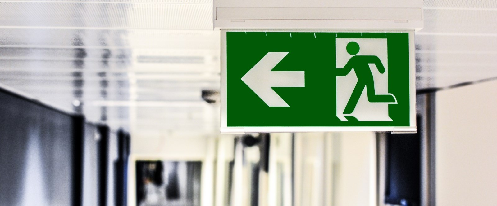 Green escape sign of person running away Cornwall