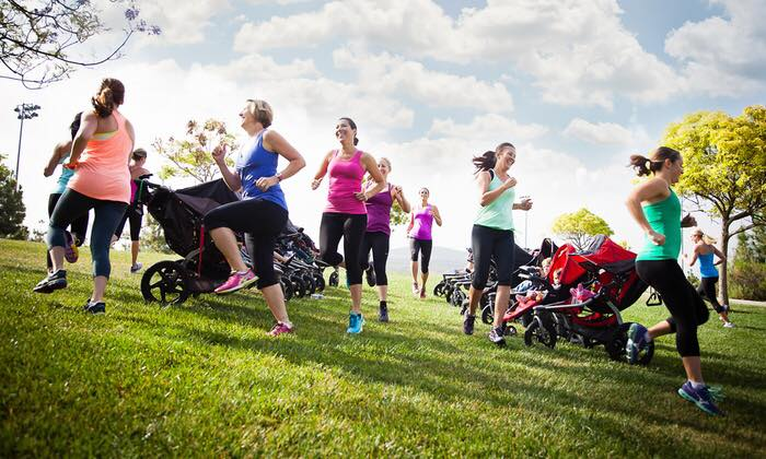 Women jog around strollers in park