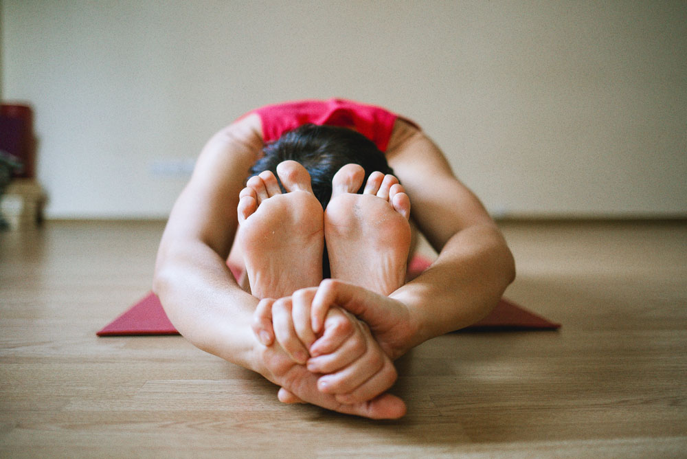 Woman bent with hands around feet in yoga pose