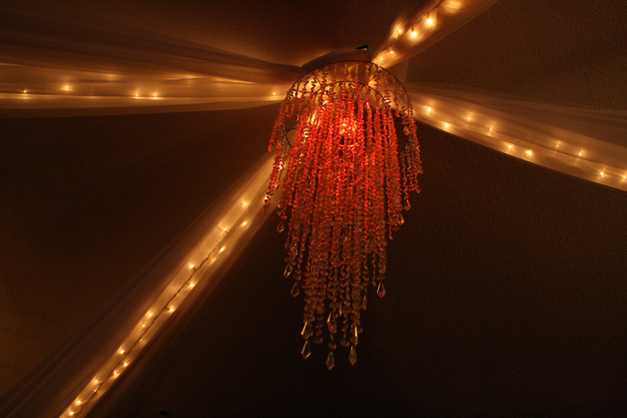 Red chandelier with white string lights on ceiling